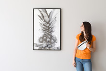 Beautiful Young Woman Standing Near Picture Hanging On Light Wall