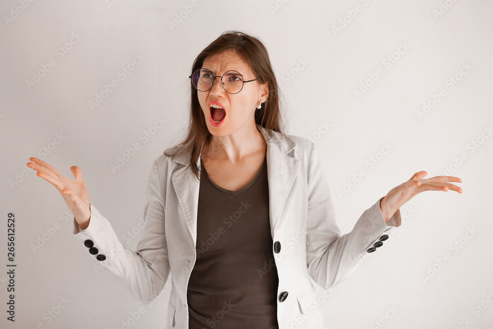 Fototapety, obrazy: Excited screaming young woman in glasses standing isolated over light gray background. Looking at camera.