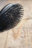 Black hairbrush with blonde hair on wooden floor. - 265617118