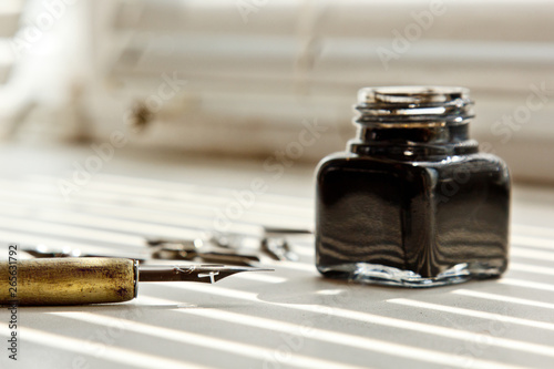 Fotografia, Obraz Inkpot with metal tips for the ink pen on a white background in solar rays