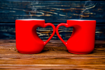 two heart shaped mugs with tea on brown background