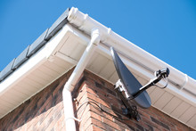 A New Installed Satellite Dish On The Side Of A Residential Building.