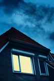House with illuminated window under dark cloudy sky in twilight. - 265638519