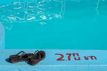 Sandals By A Swimming Pool Wit...