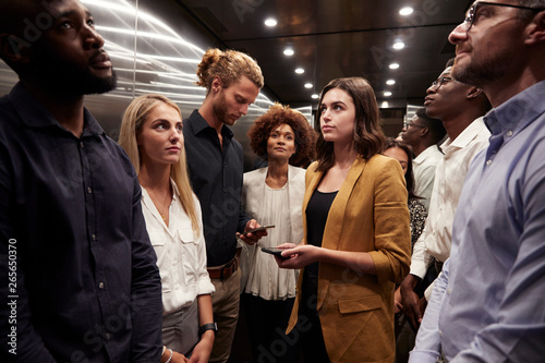Work colleagues stand waiting together in an elevator at their office - 265650370