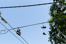 Two Pairs Of Shoes Hanging From Telephone Line Above.