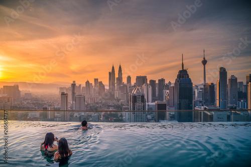 Photo Stands Kuala Lumpur Traveler looking view skyline Kuala Lumpur city in swimming pool on the roof top of hotel at sunrise in Kuala Lumpur, Malaysia.