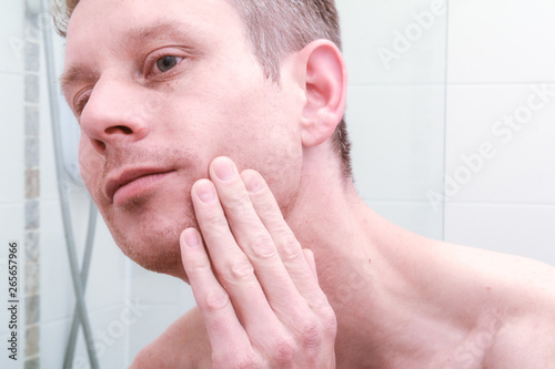 Photo Man looking in mirror and applying product to skin on face in the bathroom