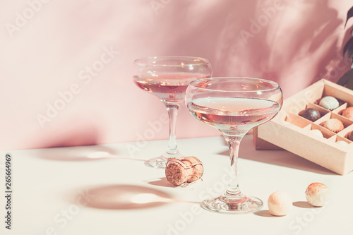 Champagne or wine in glasses box of chocolates of white and dark chocolate on pink background bright light Fototapeta