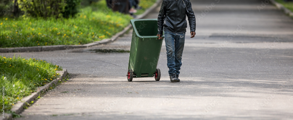 Fototapeta garbage man with trash can cleans up