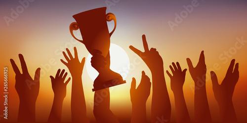 Fotografía  Concept du succès, avec une équipe de sportifs qui savourent leur victoire, en brandissant le trophée gagné lors d'une compétition sportive et en levant les bras en signe de la victoire