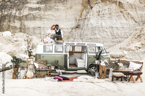 Happy young couple African man and Caucasian woman sitting on the roof of the vintage green hippy bus in the summer in the desert, canyon Wallpaper Mural