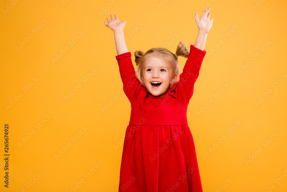 Fototapety, obrazy: baby girl portrait isolate yellow background.Stylish little baby with hands up. Portrait of shocked little girl in red dress isolated on yellow background