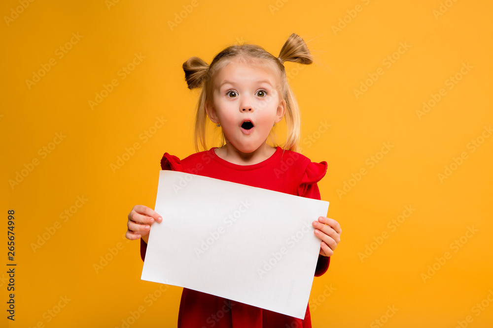 Fototapeta baby girl holding white sheet.Cute little girl with white sheet of paper.yellow background.copy spase.Little girl holding empty sheet of a paper