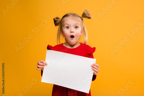 Fototapeta baby girl holding white sheet.Cute little girl with white sheet of paper.yellow background.copy spase.Little girl holding empty sheet of a paper obraz