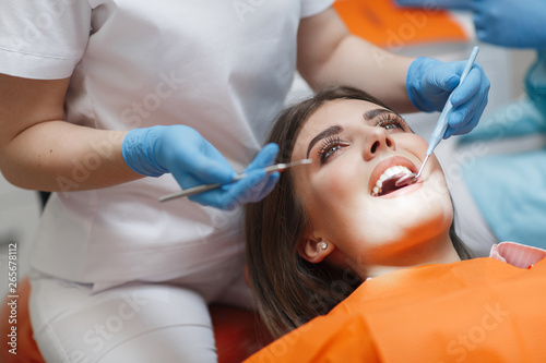 fototapeta na lodówkę Dental clinic. Reception, examination of the patient. Teeth care. Young woman undergoes a dental examination by a dentist.Happy patient and dentist concept.Female dentist in dental office talking with