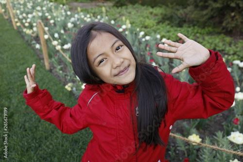 Cuadros en Lienzo Jeune fille asiatique pose en gros plan devant des fleurs avec une veste d'hiver