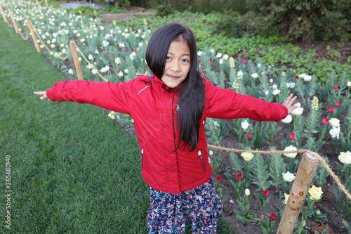 Fotografía Jeune fille asiatique pose devant des fleurs avec une veste d'hiver rouge