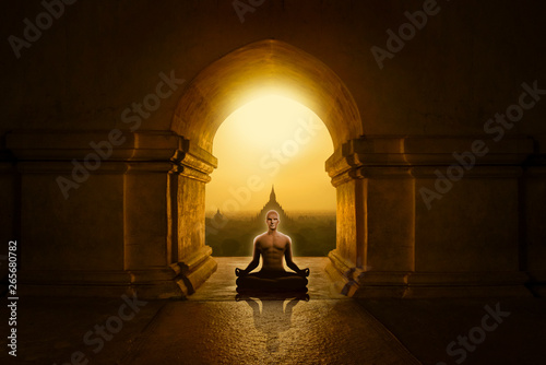 Man in yoga pose meditating in a Buddhist temple
