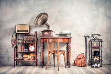 Antique chair, old typewriter, retro radio,  gramophone on wooden desk, books, clock, camera, binoculars, fiddle, keys on shelf, mask, cylinder hat, shoes, cane, backpack. Vintage style filtered photo