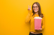 Young pretty caucasian woman fun and happy doing a gesture of victory. She is eating popcorns.