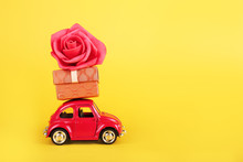 Red Retro Toy Car With Red Rose Flower On Yellow Background. Flowers, Gifts  Delivery Concept.