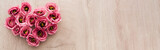 panoramic shot of heart sign made of pink eustoma flowers on wooden table with copy space