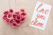 Leinwandbild Motiv top view of heart sign made of eustoma flowers and card with love you mom lettering on wooden table
