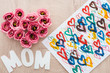 Leinwanddruck Bild - top view of heart sign made of eustoma flowers, drawing and mom sign on wooden table