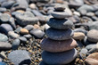 a pyramid of pebbles on a blurred background of stones