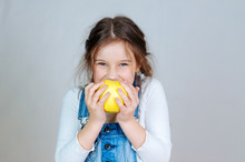 Emotional Portrait Little Beautiful Girl With Pigtails In Jeans Overalls Eating Bites Holding An Apple. 6-7 Years Studio