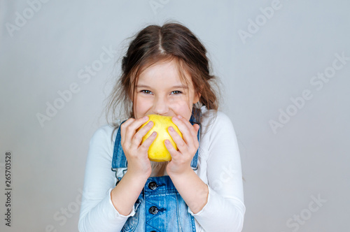 Photo  Emotional portrait little beautiful girl with pigtails in jeans overalls eating bites holding an apple