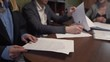 Close Up Hands of Couple Before Signing Contracts for New Real Estate Property in Realtors Office. Light Camera Movement