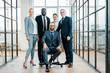 handsome bearded businessman sitting on chair near multicultural coworkers