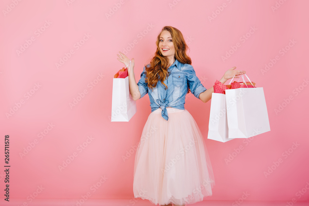 Fototapeta Portrait of female shopaholic holding paper bags from favorite stores and smiling, isolated on pink background. Attractive young woman with curly hair comes back from shopping carrying packages