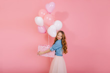 Charming Birthday Girl In Denim Shirt With Eyes Closed Holds A Large Gift Box Guessing What's Inside. Portrait Of Attractive Long-haired Young Woman In Lush Skirt, Standing With Present And Balloons