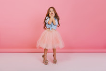 Lovely Moments Of Cute Little Astonished Girl Expressing To Camera Isolated On Pink Background. Wearing Mothers Shoes, Fashionable Young Child In Tulle Skirt, Blue Jeans Shirt