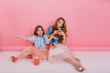 Cute Brunette Girl Having Fun With Her Stylish Mom In Lush Skirt And Drinks Cocktail At Birthday Party. Young Mother And Happy Daughter Playing Together And Enjoys Tasty Berry Juice On Pink Background