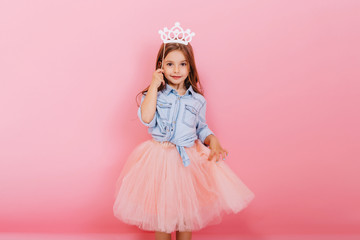 Cheerful little girl with long brunette hair in tulle skirt holding princess crown on head  isolated on pink background. Celebrating brightful carnival for kids, birthday party, having fun of cute kid