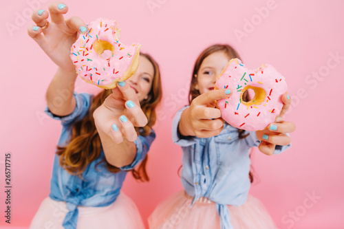 Young cheerful mother and cute smiling daughter having fun with tasty donuts waiting for tea party with family. Little girl with her mom showing doughnuts wich they cooked together and laughing