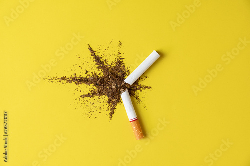 Cuadros en Lienzo Close up cigarette broken tobacco blast spread on yellow pastel background with light side and little shadow