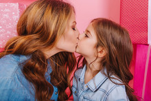 Portrait Of Little Brunette Girl In Trendy Vintage Jacket Kissing Her Young Mother In The  Same Outfit. Adorable Curly Woman Congratulates Her Daughter With Birthday Posing With Giftes On Background