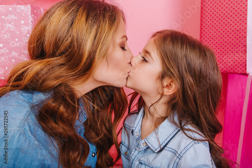 Carta da parati Portrait of little brunette girl in trendy vintage jacket kissing her young mother in the  same outfit