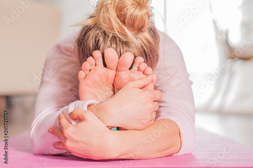 Photo Woman practicing yoga, seated forward bend pose, doing paschimottanasana exercis