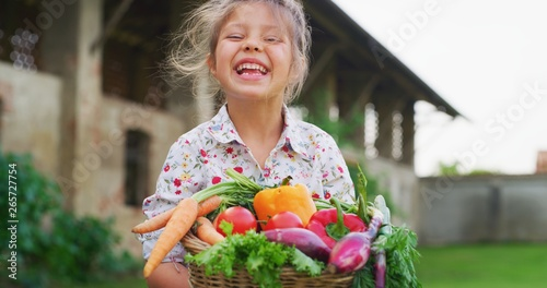 Portrait of happy little girl is holding a basket with fresh biologic just harvested vegetables and smiling in camera on a background of a countryside farm.