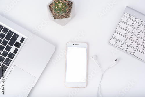 Valokuva  Modern white office work table with smartphone mock up laptop ,earphone and catu