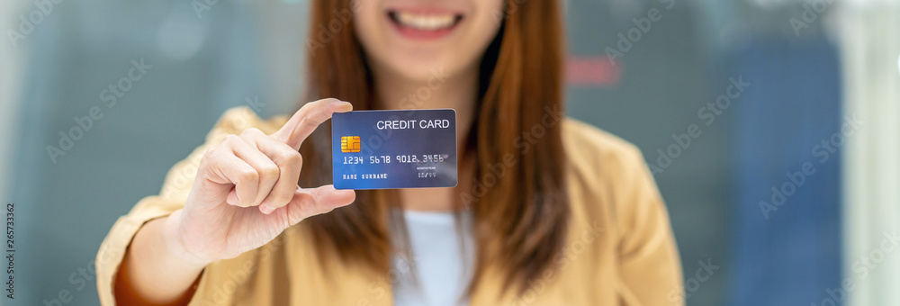 Fototapeta Banner of Asian woman holding and presenting the credit card for online shopping in department store over the clothes shop store, technology money wallet and online payment concept, credit card mockup
