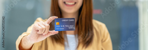 Fototapeta Banner of Asian woman holding and presenting the credit card for online shopping in department store over the clothes shop store, technology money wallet and online payment concept, credit card mockup obraz