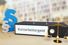 Kurzarbeitergeld – Recht/Gesetz. Ordner Auf Schreibtisch Mit Beschriftung Neben Paragraf Und Waage. Anwalt