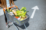 Man riding shopping cart full of fresh and healthy products outdoors, close-up view